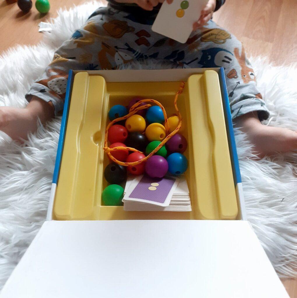 """Dziecko bawiące się zabawką """"Nawlekaj nie czekaj"""". W pudełku kilka kolorowych kulek do nawlekania wraz ze sznurkiem oraz etykietami."""