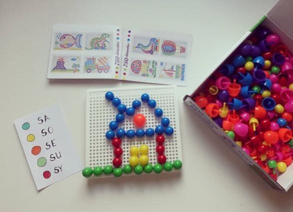 Plastikowa tablica z otworkami, w które wbite są kolorowe wpinki. Z wpinek ułożony szablon domu.