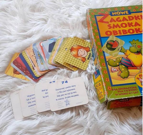 """Pudełko """"Zagadki Smoka Obiboka"""" obok kilka kart z obrazkami i kilka odwróconych kart z zapisanymi zagadkami."""