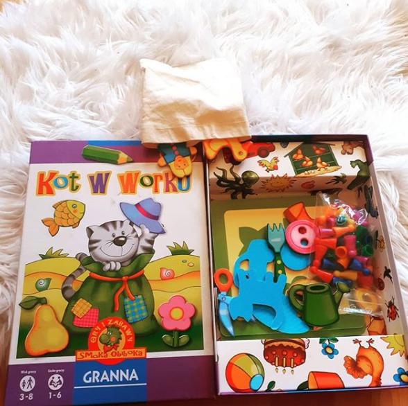 Pudełko, w którym znajdują się kartonowe obrazki przedmiotów oraz kolorowe pionki.