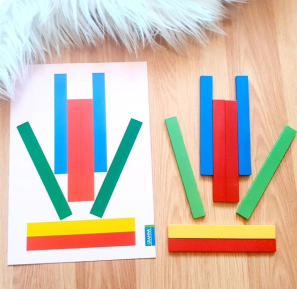 Karta główna z ułożonym z kolorowych patyków wzorem obok kolorowe drewniane patyczki odtwarzające układ z karty.